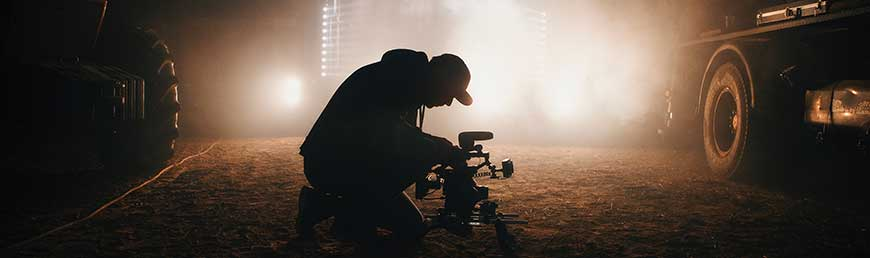 the-ultimate-video-essay-checklist-tools-video-essay-banner.-person-setting-up-camera-in-front-of-lights-in-a-barn